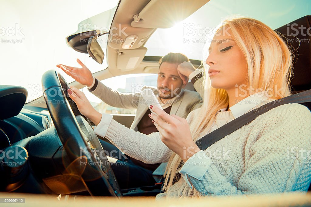 Woman typing text message while driving a car stock photo