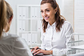 Woman typing while looking at her colleague