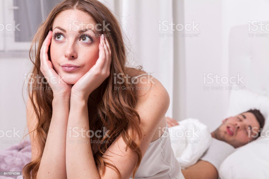 woman unable to sleep while man snoring in bed stock photo