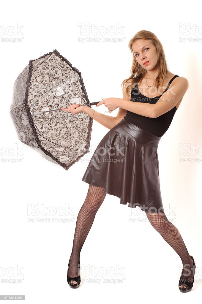 Woman under black umbrella against the white wall stock photo