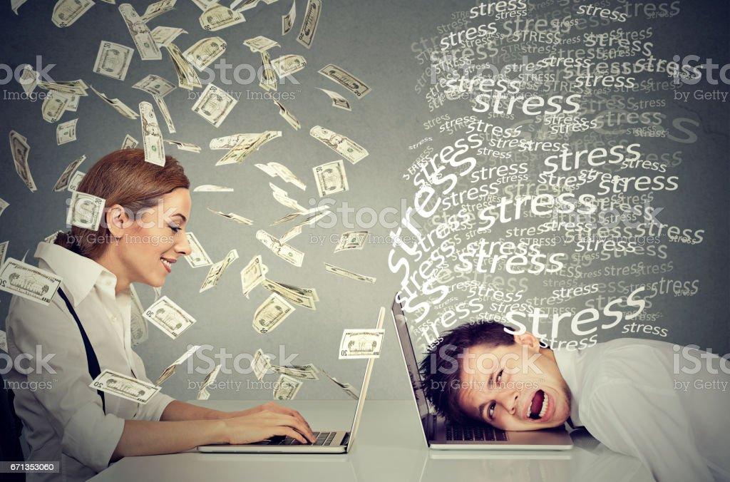 Woman under cash rain working on laptop making money next to stressed man stock photo