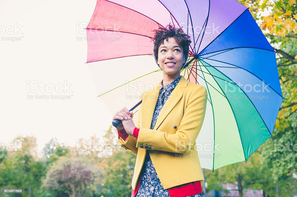 Woman under colorful umbrella in a park (London, UK) stock photo