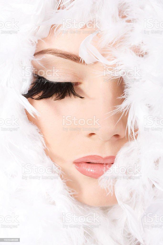 Woman under feathers wearing long false eyelashes stock photo