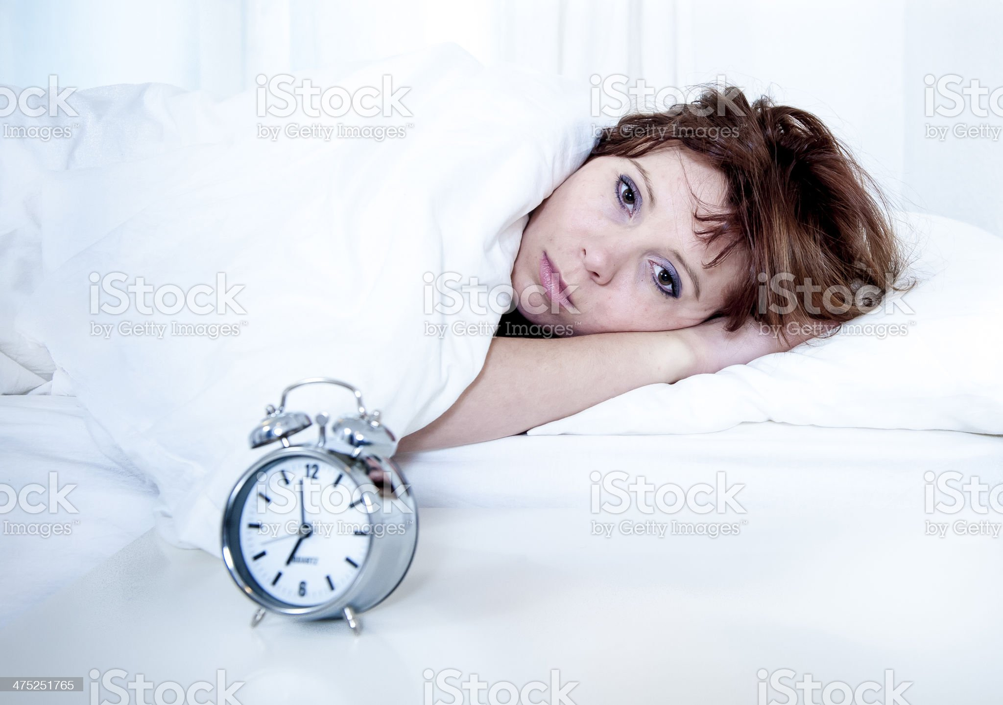 Woman under in bed with alarm clock royalty-free stock photo