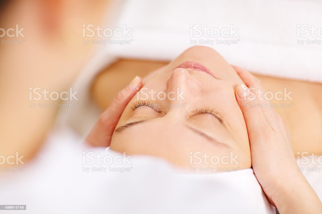 Woman under professional facial massage in beauty spa stock photo