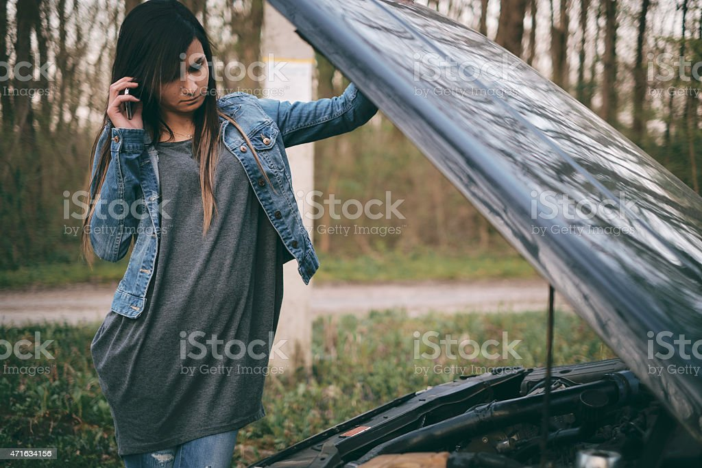 Woman under the hood of her car break down stock photo