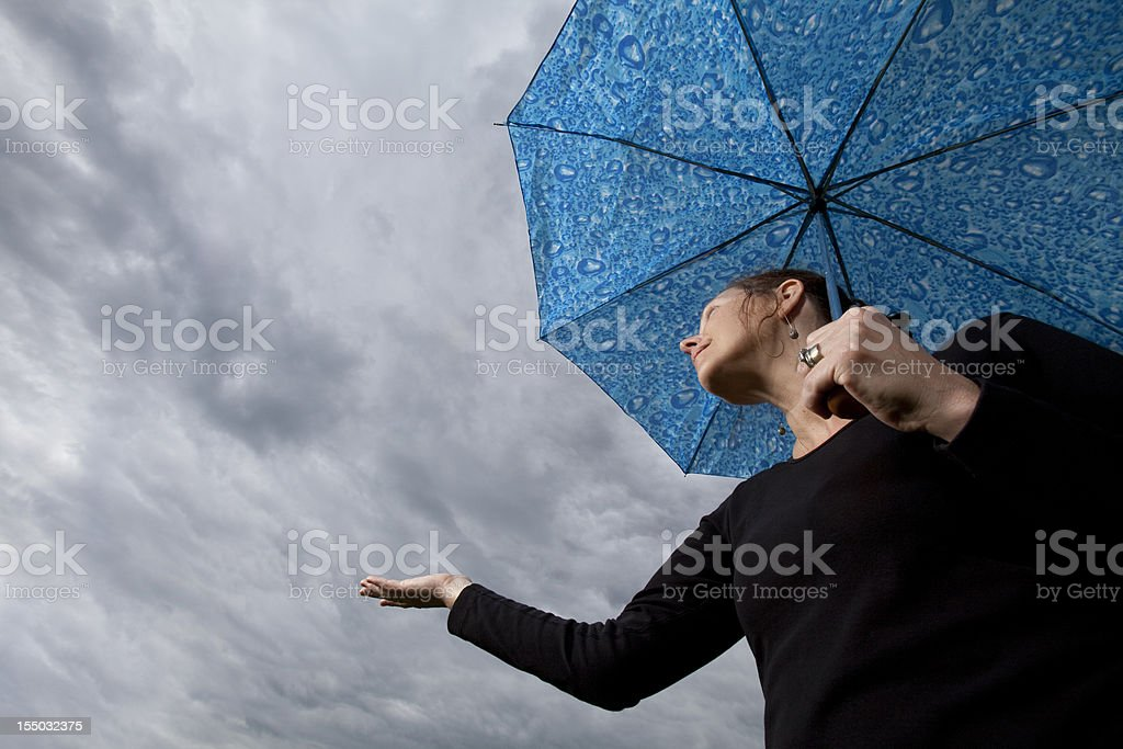 Woman under umbrella holding hand out to check for rain stock photo