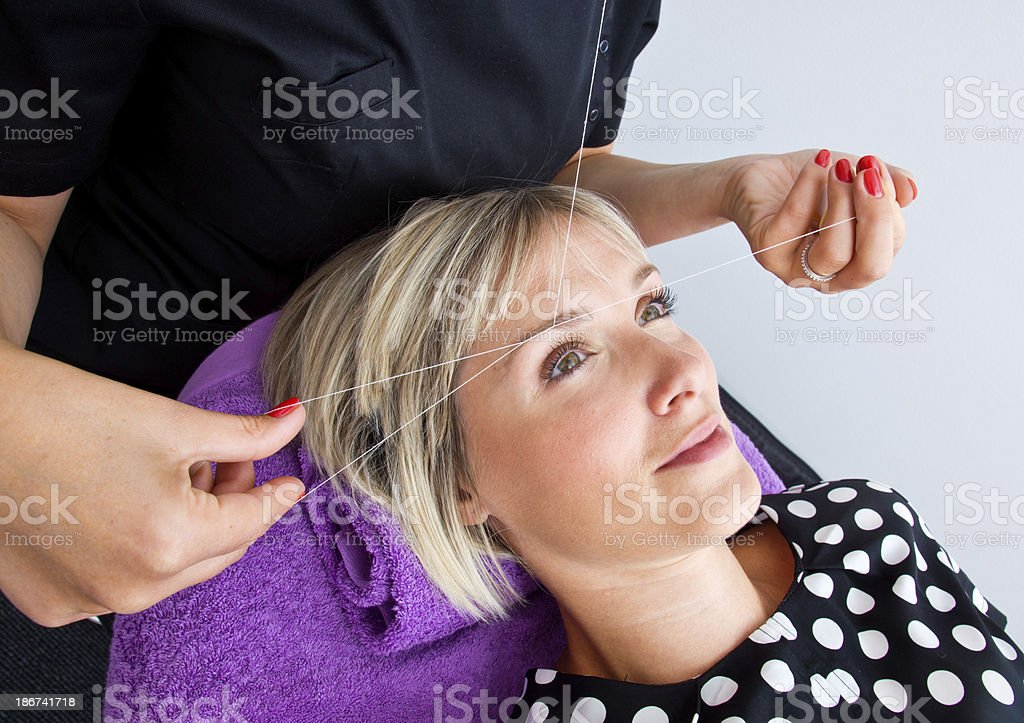 Woman undergoing threading hair removal procedure stock photo