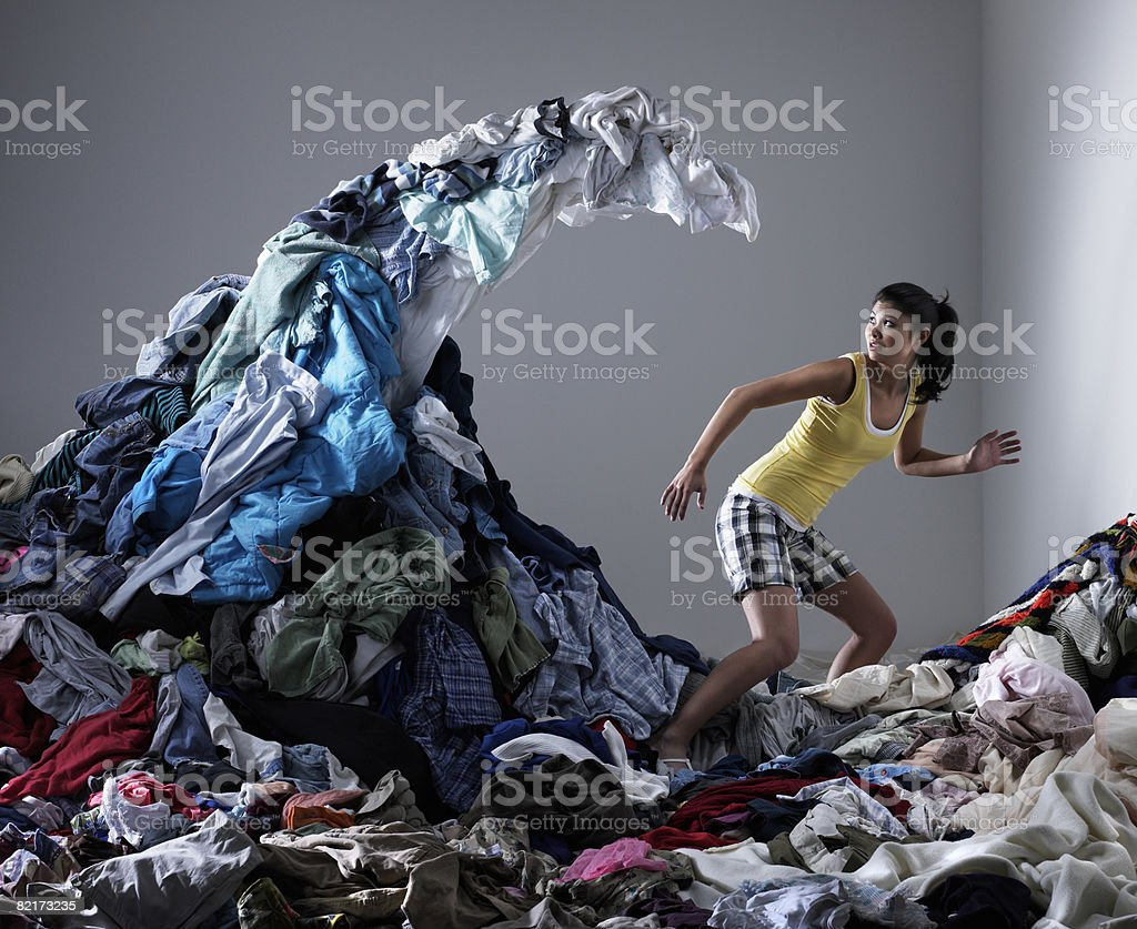 Woman underneath wave of laundry stock photo