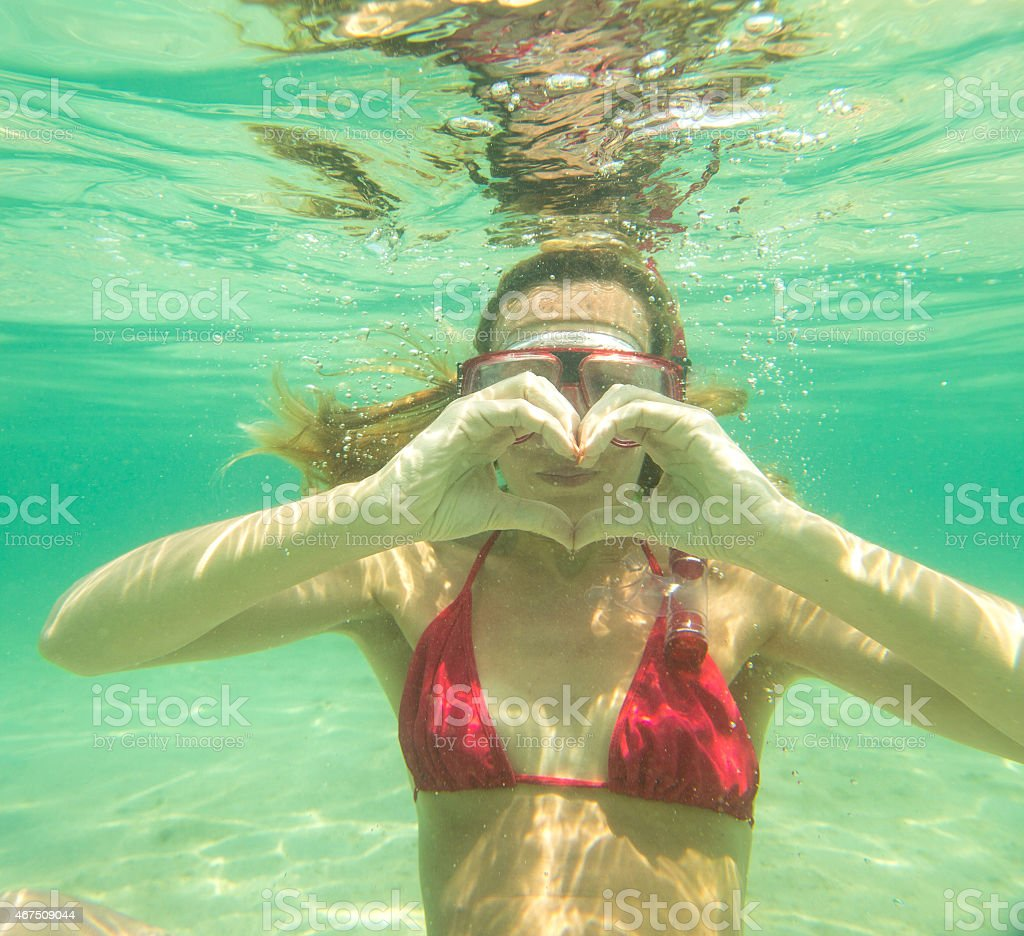Woman underwater making heart shape with hands stock photo