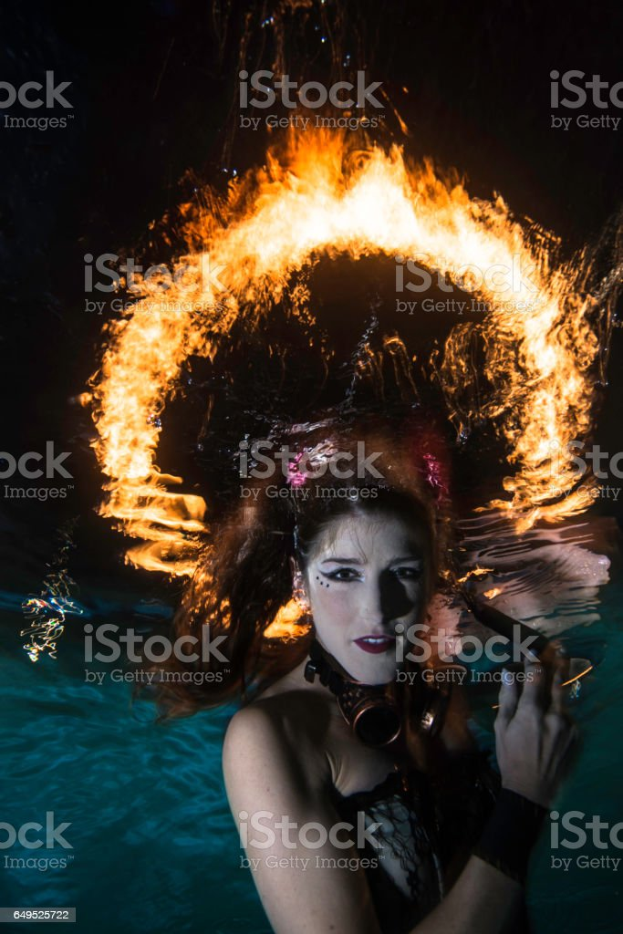 Woman underwater posing with a ring of fire in the background stock photo
