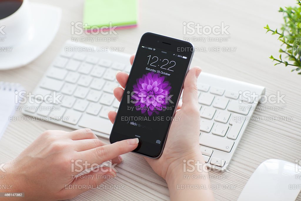 Woman unlock iPhone 6 Space Gray over the table stock photo