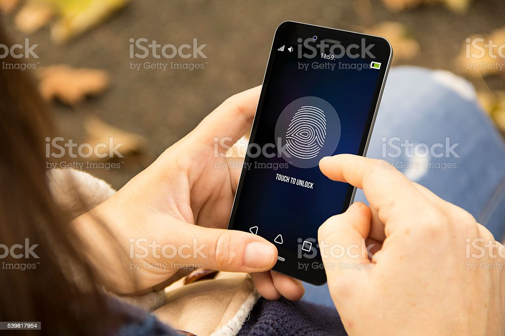 woman unlocking phone in the park stock photo