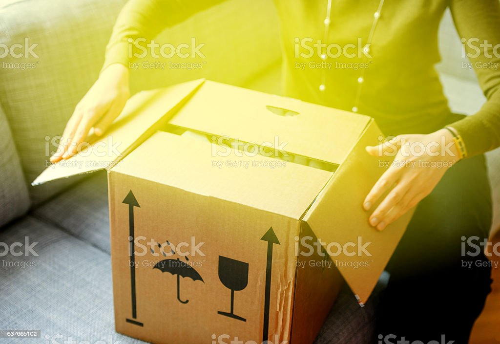 Woman unpacking unboxing cardboard box surprise stock photo