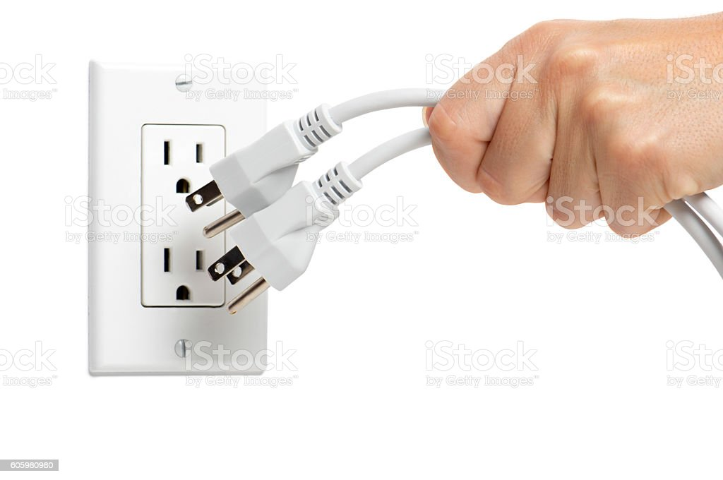 woman unplugging electrical cords on white stock photo