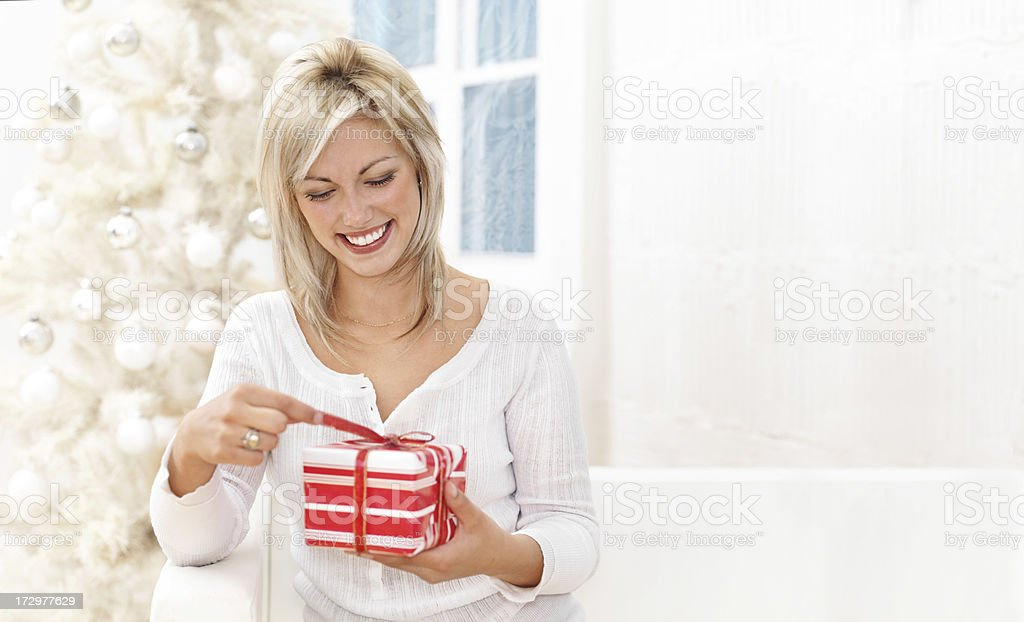 Woman Unwrapping Xmas Gift royalty-free stock photo
