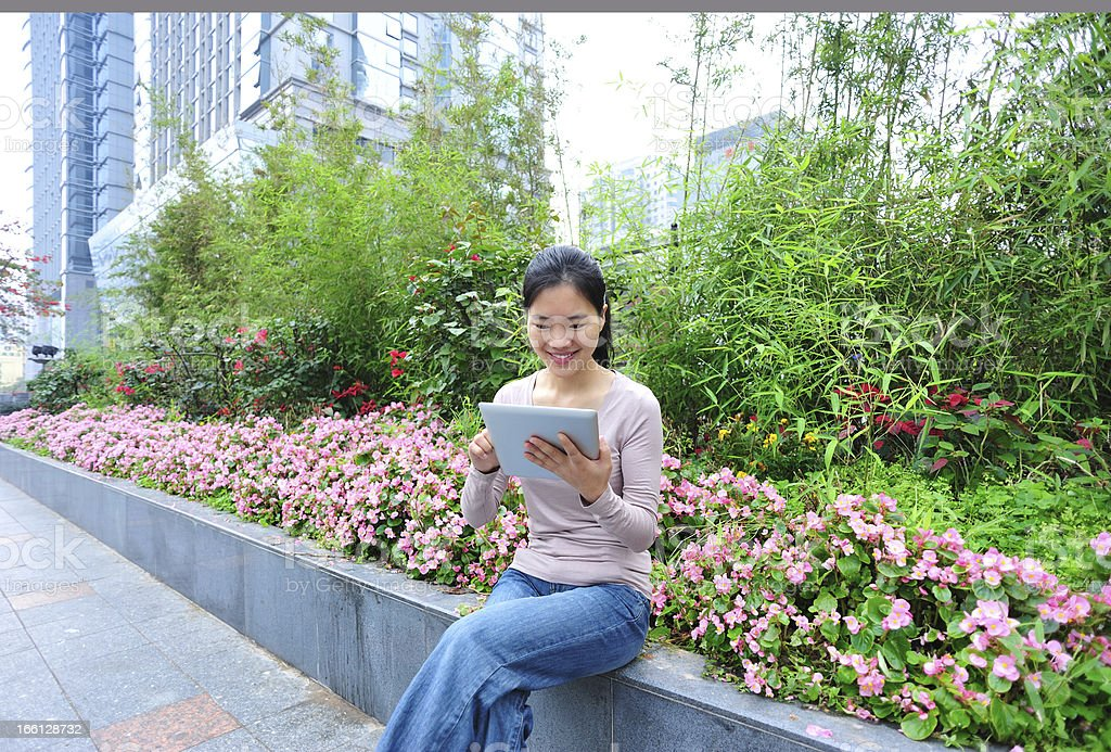 woman use digital tablet in city garden royalty-free stock photo