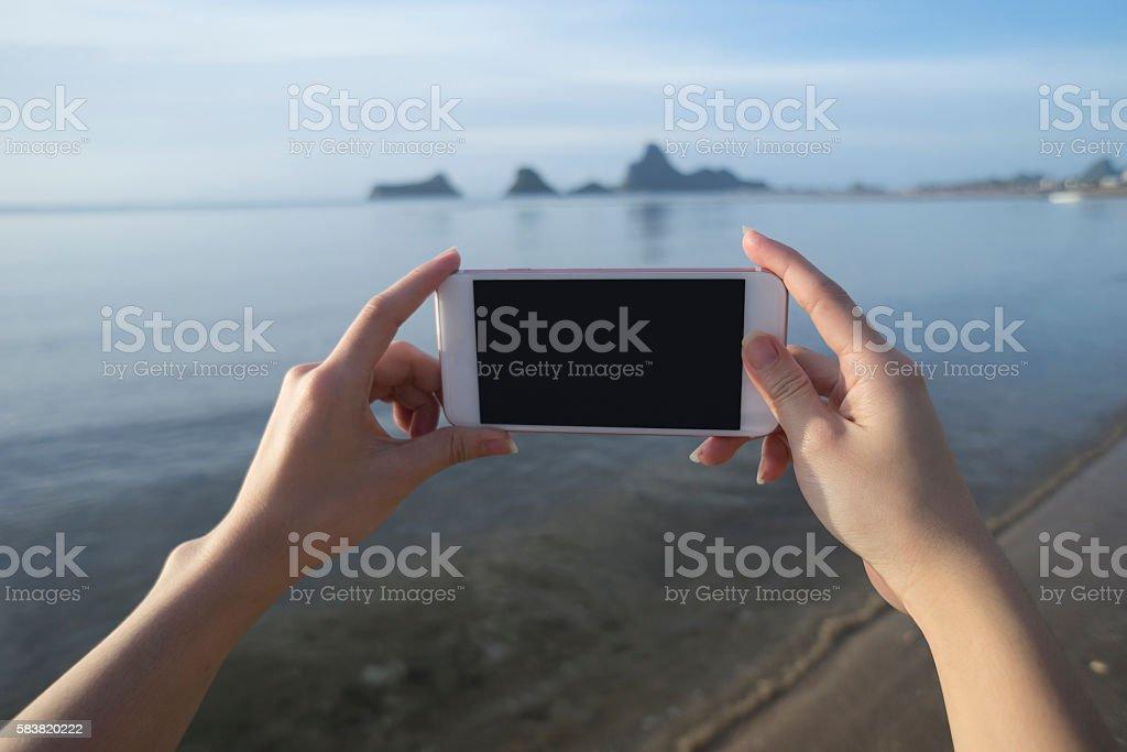 woman use smart phone take a photo of the sea stock photo