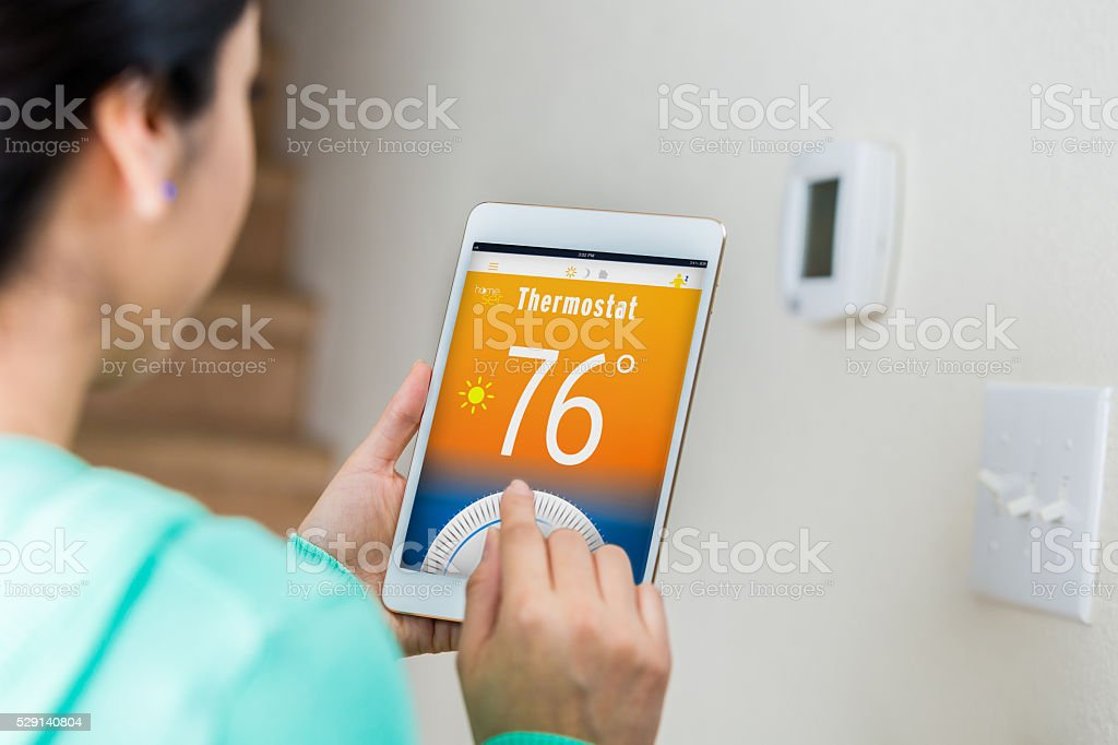 Woman uses digital tablet to control home's temperature stock photo