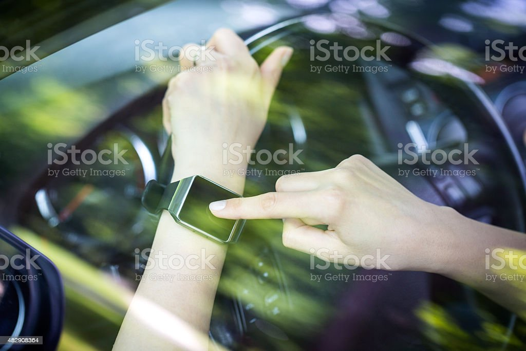 Woman uses smartwatch in the car. stock photo