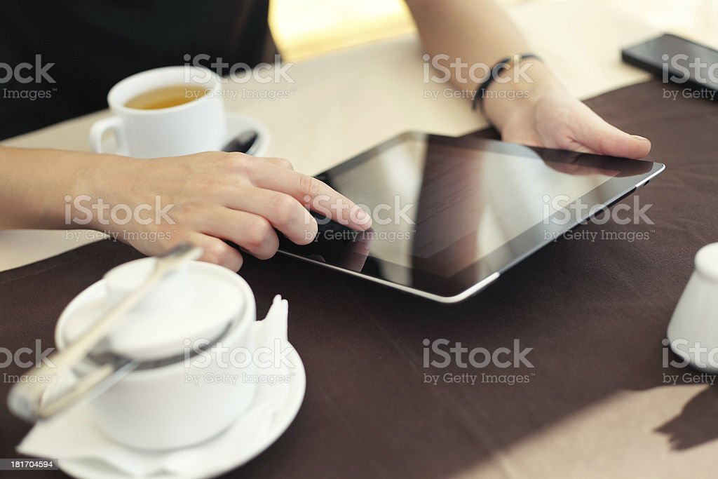 Woman uses tablet and drinks coffee at cafe royalty-free stock photo