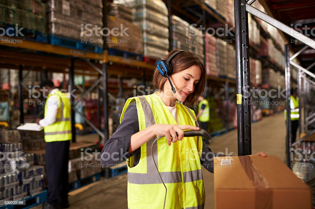 Woman using a barcode reader in a distribution warehouse stock photo