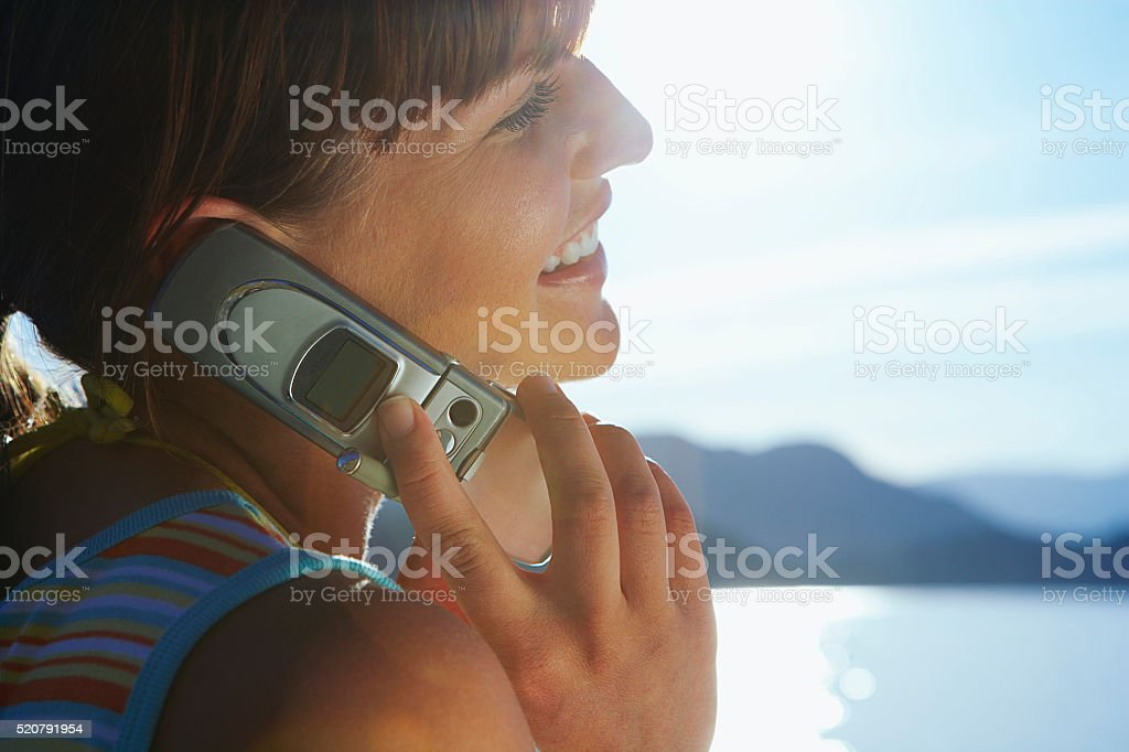 Woman using a cell phone at the beach stock photo