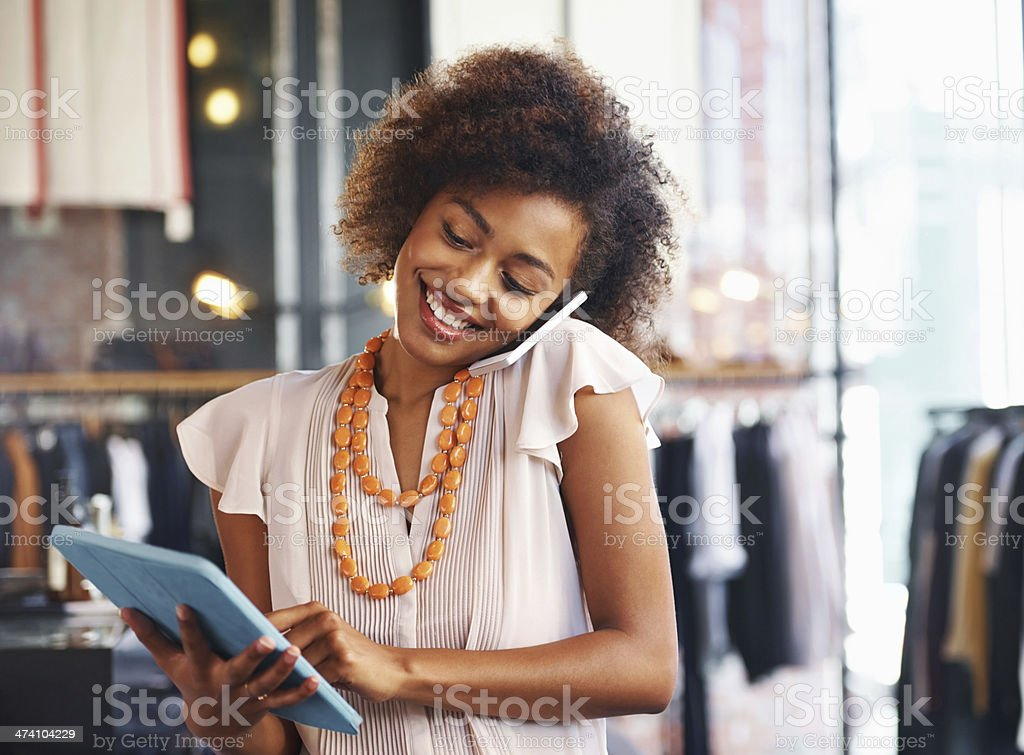 Woman using a digital tablet and talking on phone stock photo