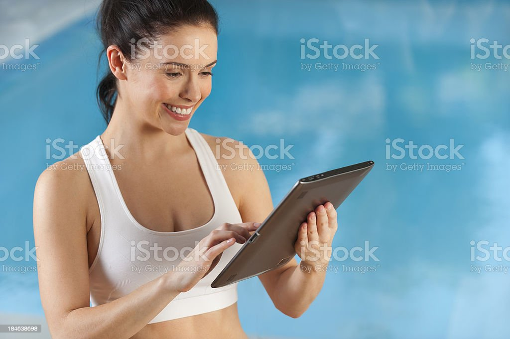Woman using a digital tablet at the gym royalty-free stock photo