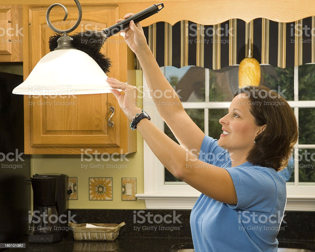 A woman using a feather duster to clean a light shade stock photo