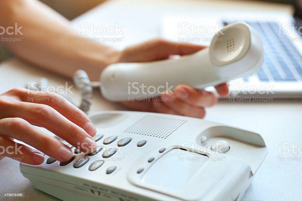 A woman using a landline phone stock photo