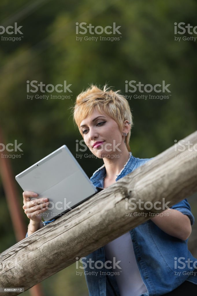 woman using a laptop tablet outdoors stock photo