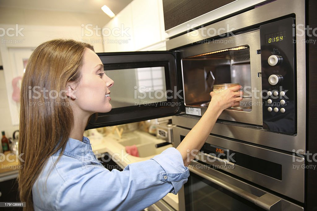 Woman using a microwave in kitchen stock photo