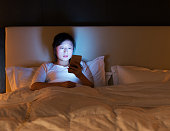 Woman using a smart phone in bed