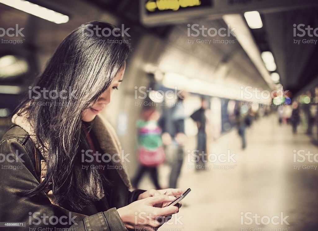woman using a smartphone on the metro subway station stock photo
