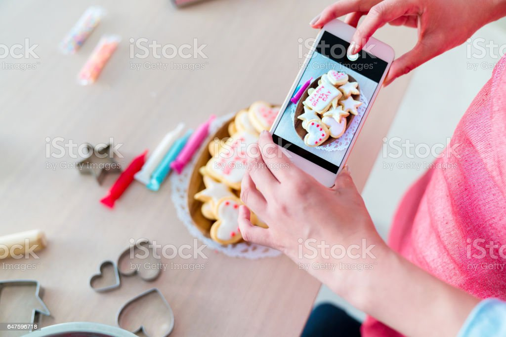 Woman using a smartphone to take a photo of freshly decorated cookies stock photo