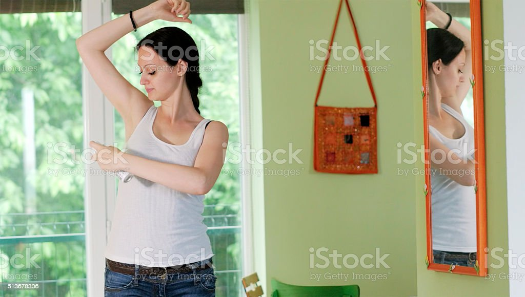 Woman using a spray can deodorant stock photo