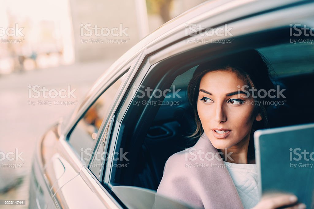 Woman using a tablet in a car stock photo