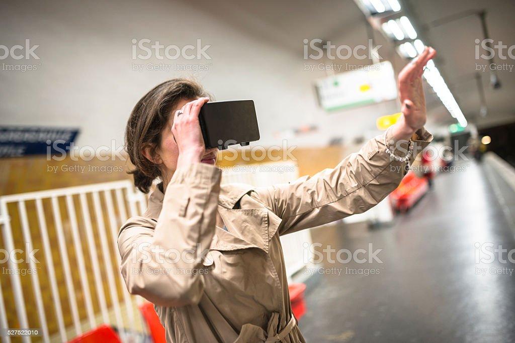 woman using a Virtual reality simulator inside a subway station stock photo