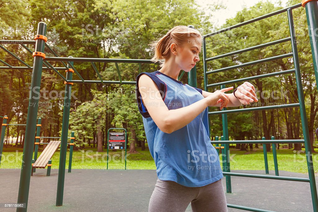 Woman using activity tracker at gym stock photo