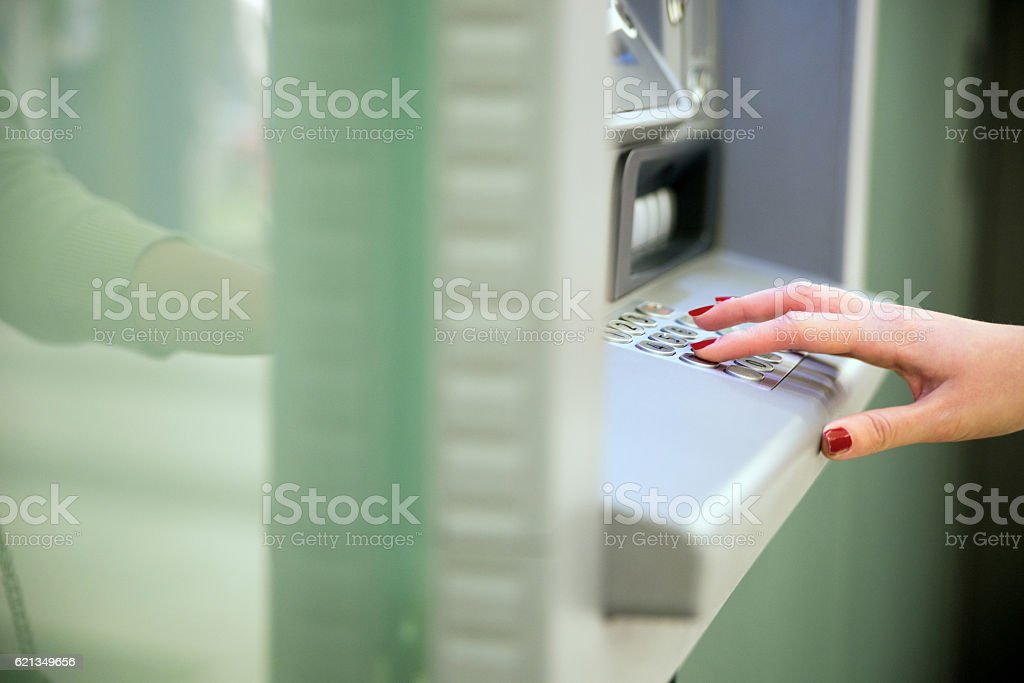 Woman Using an Automated Teller Machine in shopping center stock photo