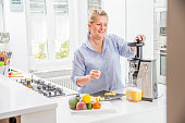 Woman using an Electric Juicer in her Kitchen