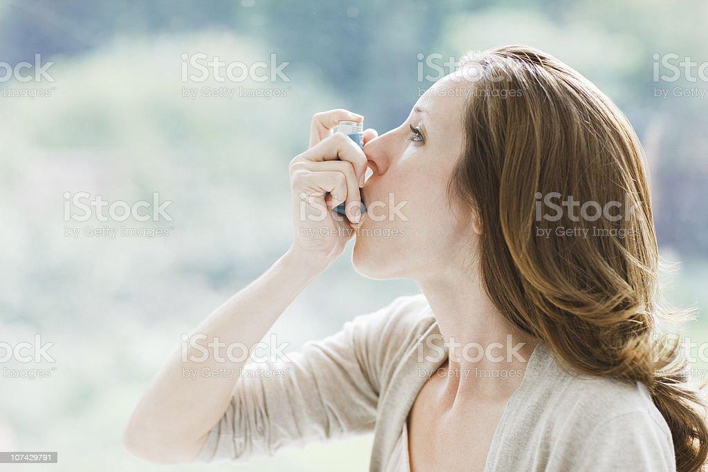 Woman using asthma inhaler stock photo