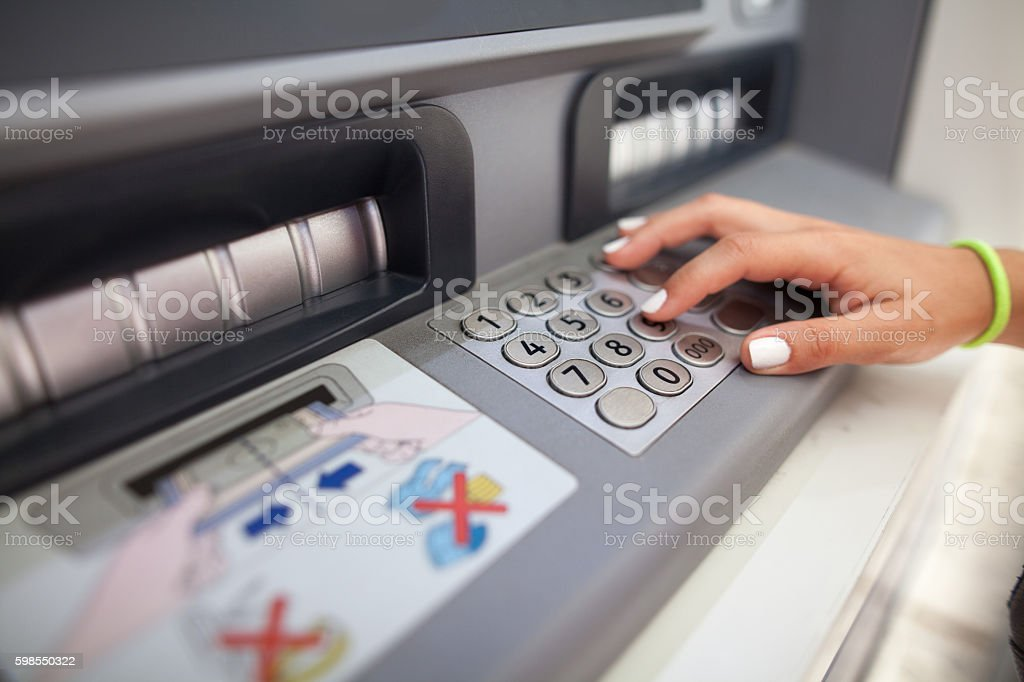 Woman using ATM machine stock photo