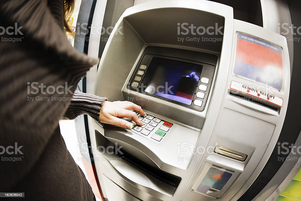 Woman using ATM, shot with fish-eye lens royalty-free stock photo