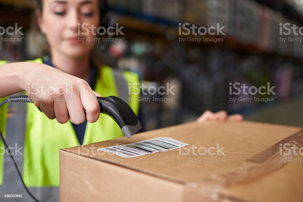 Woman using barcode reader on a box in a warehouse, detail stock photo