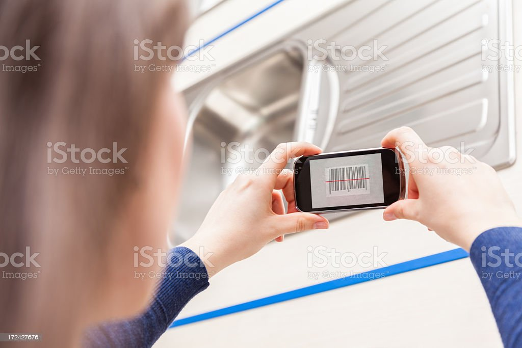 Woman Using Barcode Reader Through Cell Phone stock photo