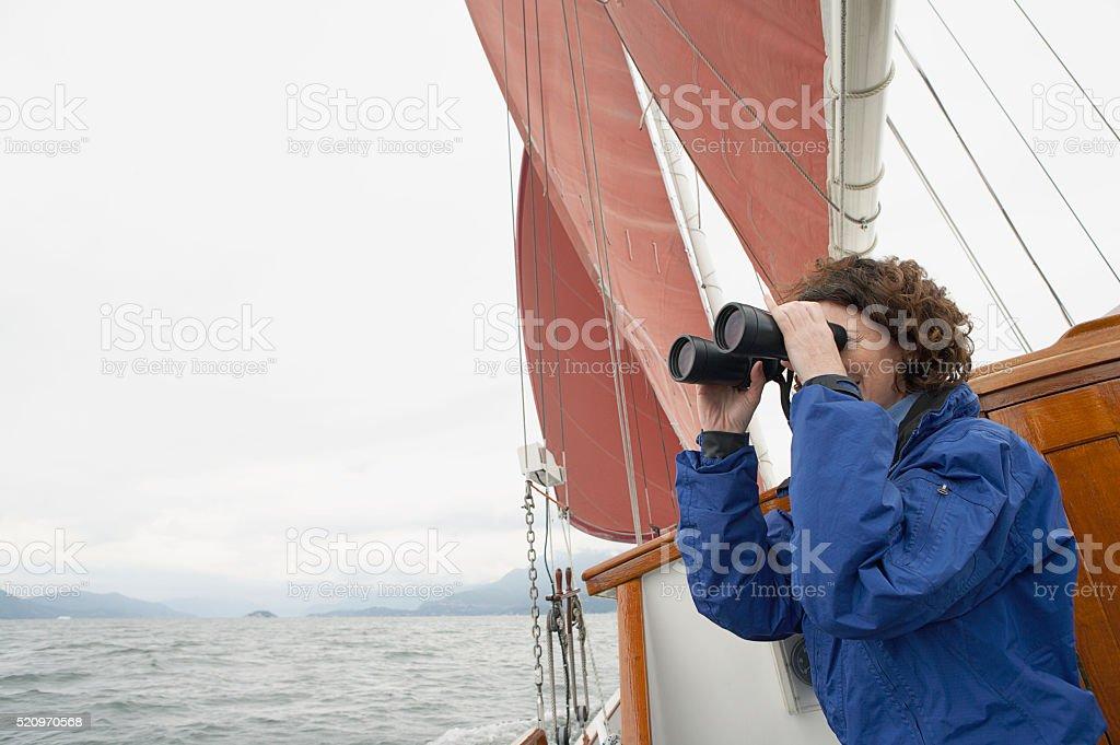 Woman using binoculars on a sailboat stock photo