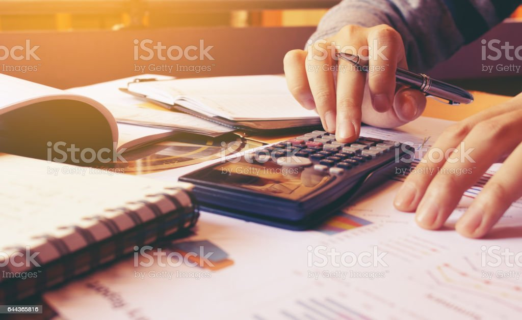 Woman using calculator with doing finance at home office. stock photo
