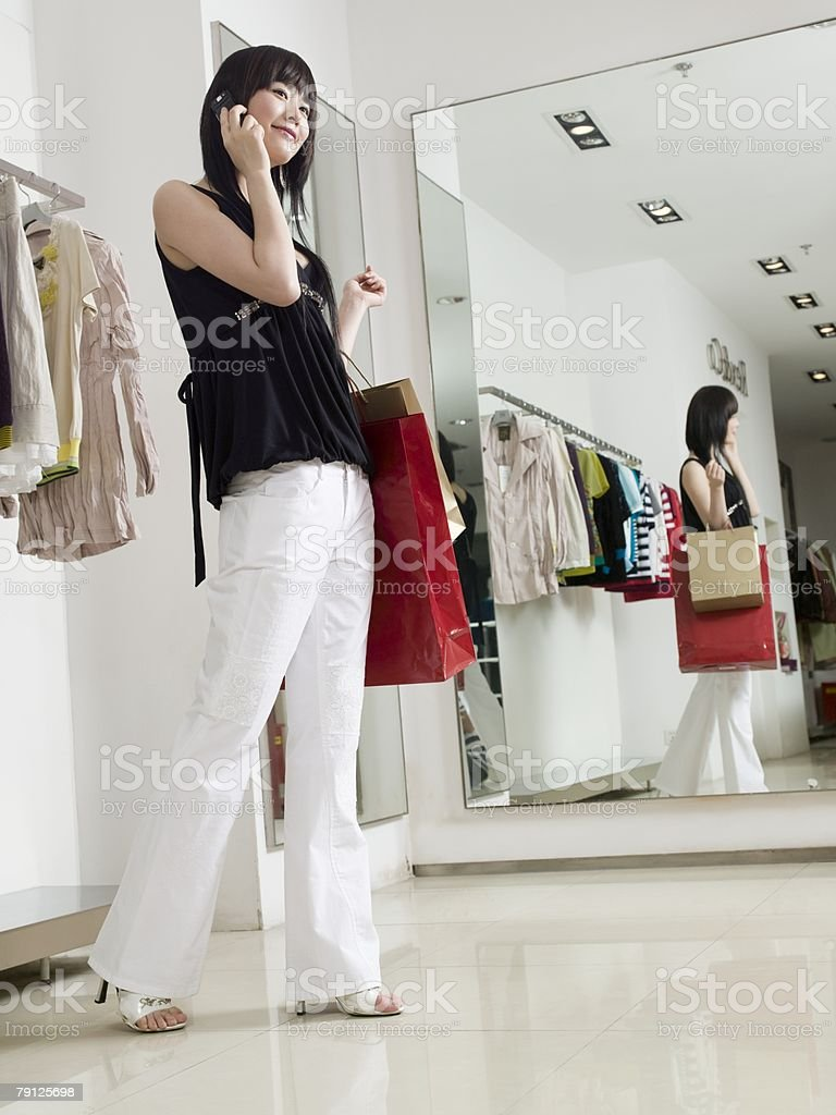Woman using cell phone in clothes store royalty-free stock photo